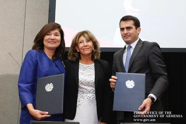 Three people standing with MOU copies